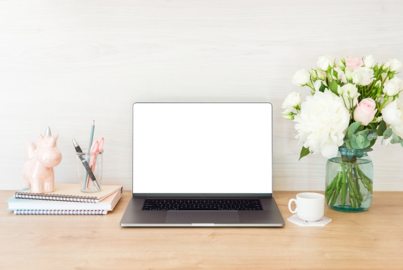 clean and organized desktop with notebooks, laptop, and vase of flowers