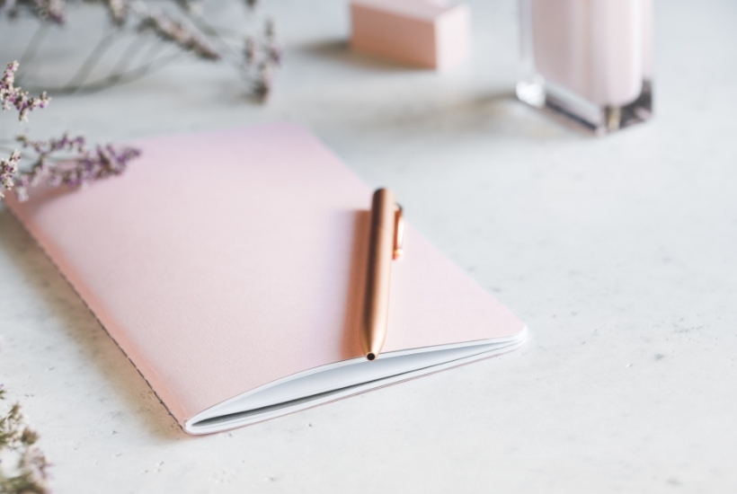light pink journal with a gold pen resting on a white desk top