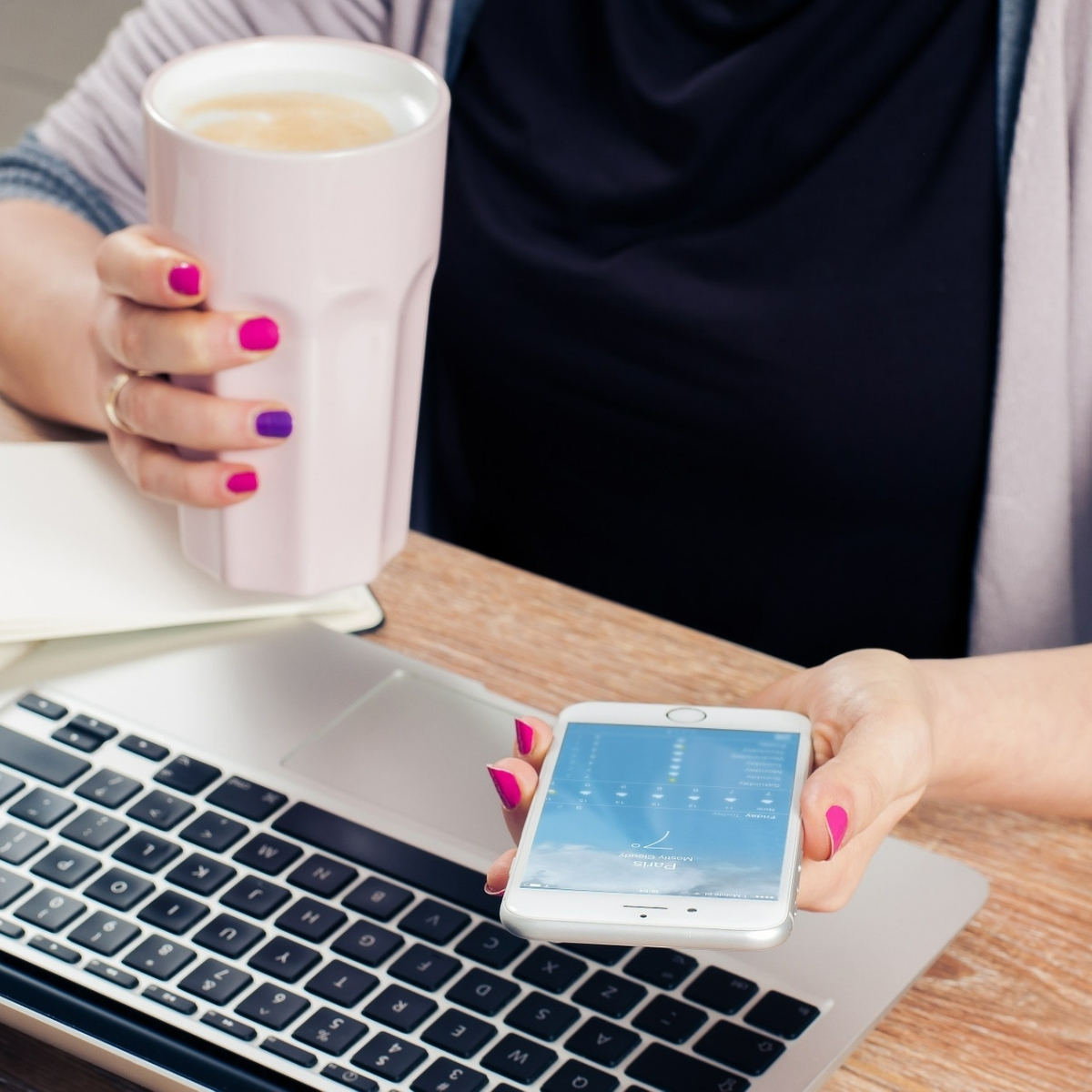 lady working at desk with a cup of coffee in hand and smartphone