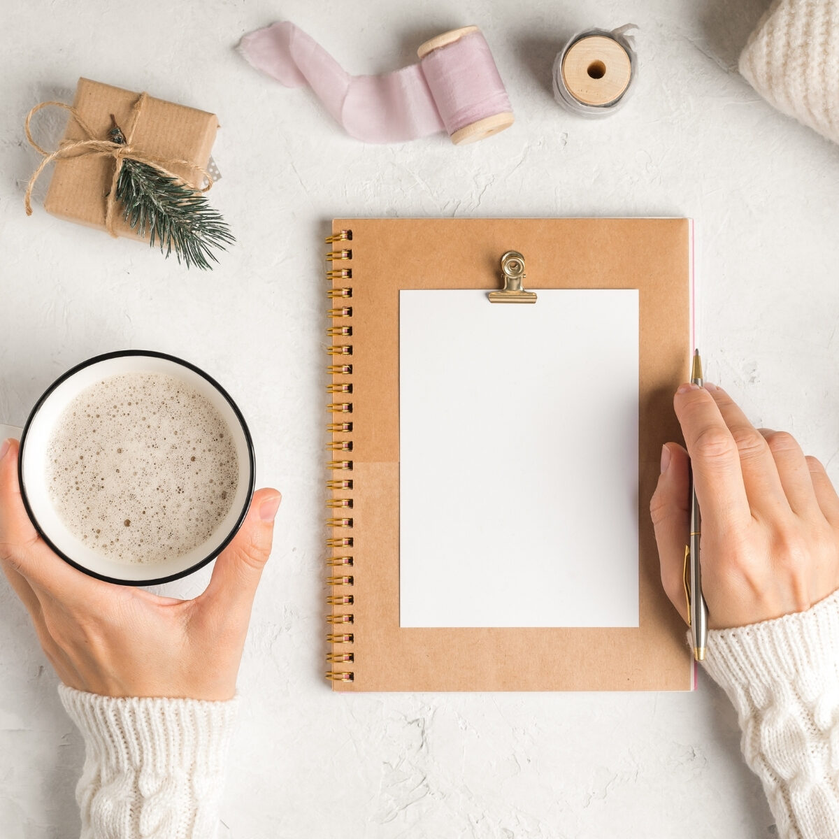lady writing in notebook with a cup of coffee in hand