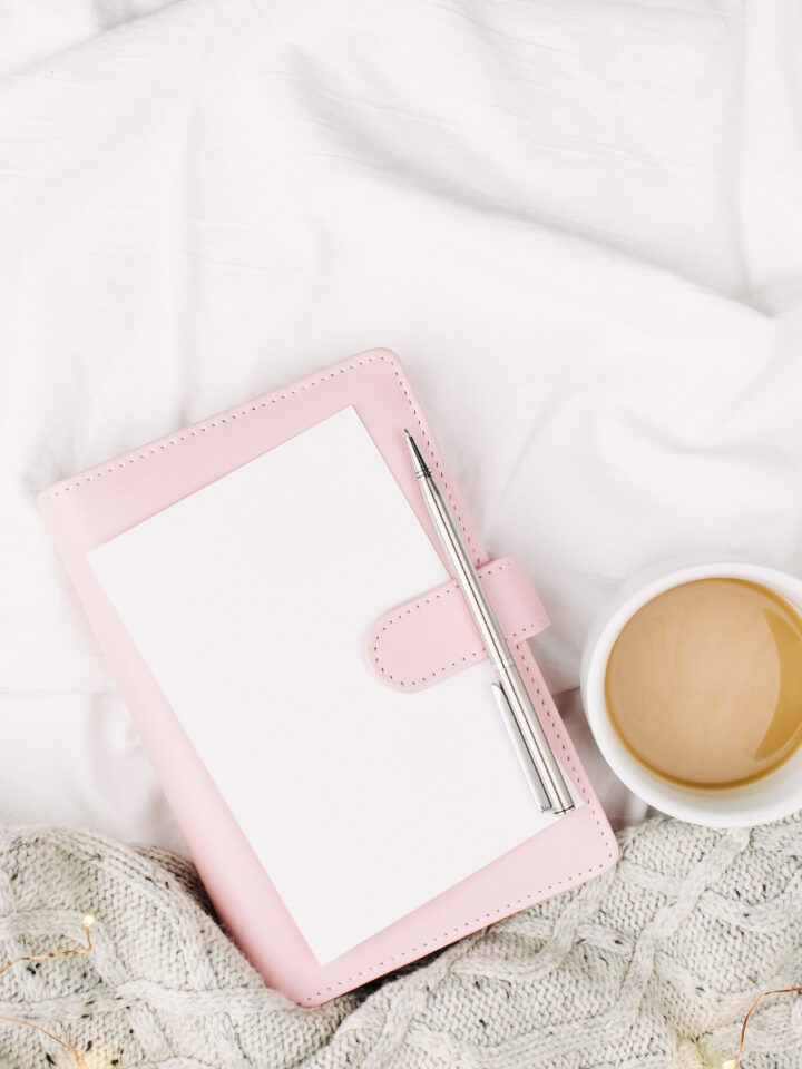 light pink planner with a white coffee mug filled with coffee